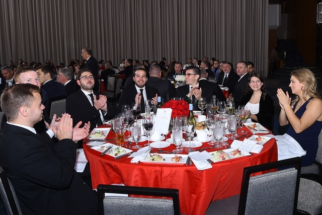 Seated guests at a table clapping