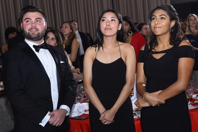 Three guests standing up at a table at the St. John's University 2019 President's Dinner