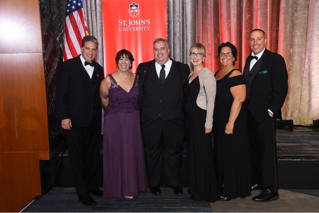 Six guests pose for a picture onstage at the St. John's University 2019 President's Dinner