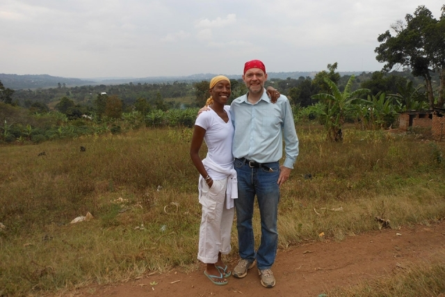 Man and woman pose for a picture outside in Uganda in a field