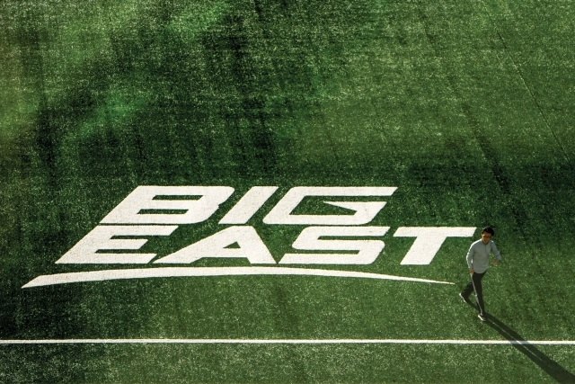 Student walking across field with BIG EAST painted on field