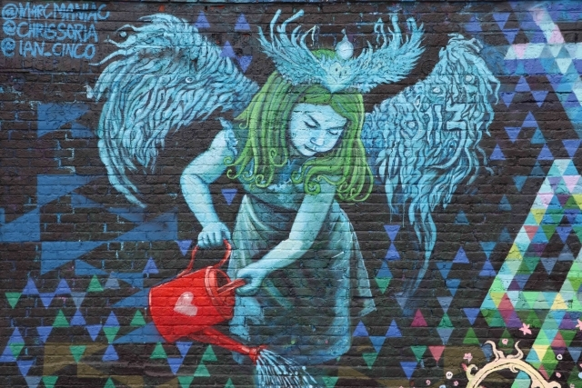 Mural of female angel holding watering can