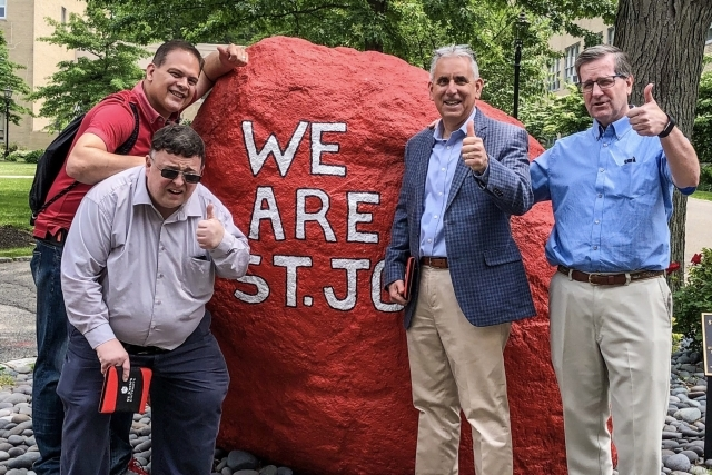 4 Men standing infront of We Are St. John's Sprit Rock