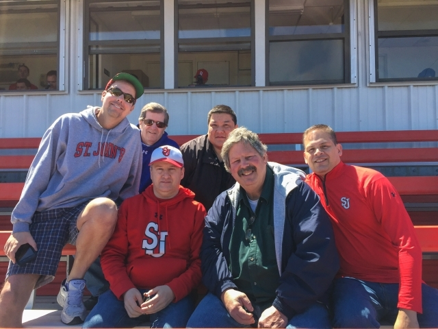 Alumni Wendell Cruz, Darrin Kneute, Mike Maher and Brian Tighe in bleachers attending a baseball game