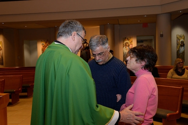 Alumni couple being blessed by Fr. Griffin during The Blessing of the Couples event
