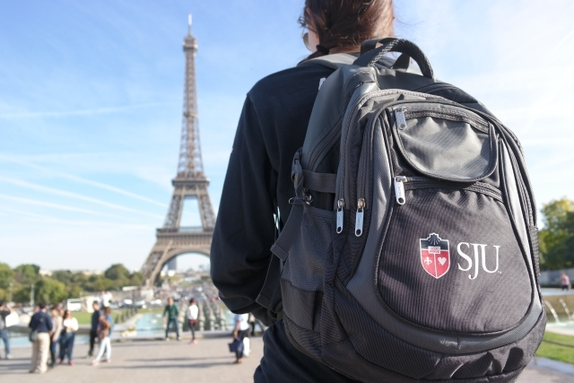 Student with SJU backpack looking at the Eiffel Tower