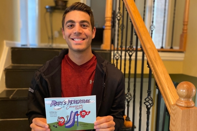 "Zachary Levy sitting on a set of stairs holding his book ""Rory's Adventures of the Cardiovascular System"""