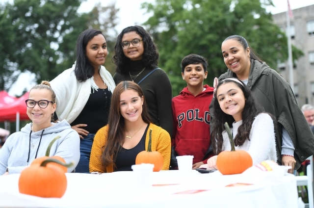 Group shot of 7 student and family members painting pumpkins