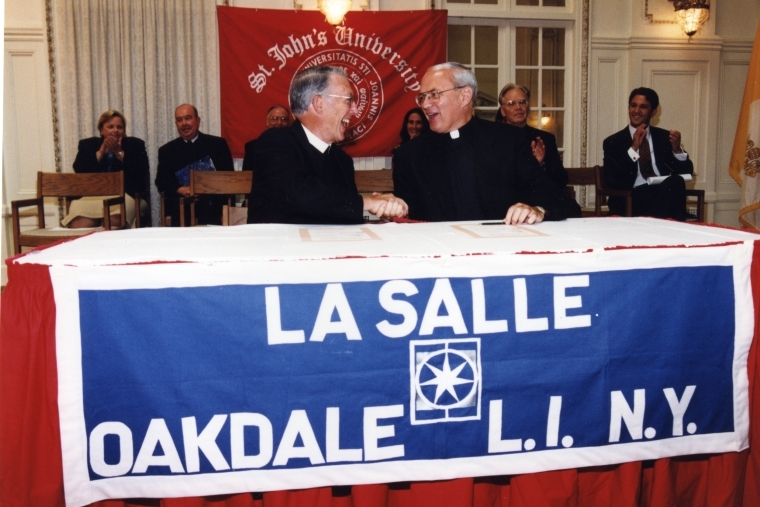 Brother A. Jerome Corrigan, left, shakes hands with Rev. Donald J. Harrington, CM, right, sitting at a table draped with a La Salle banner, and a St. John's University banner on the wall