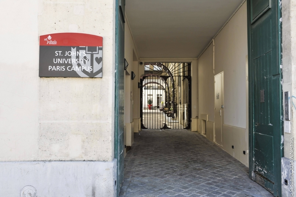 Entrance to the St. John's University Paris Campus, looking down an alley with iron gates