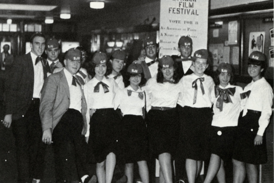 A group of students wearing red beanies and red bowties as part of the required freshman hazing in 1965.