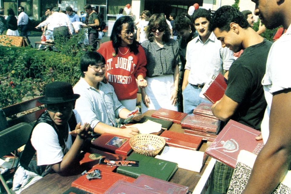 A student shows their school spirit with a red  St. John's sweatshirt and a few student organization pins at the activity fair, c. 1990.