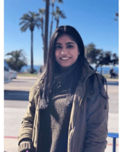Picture of Simranpreet Waraich outside in a coat, with blue sky and palm trees in the background.