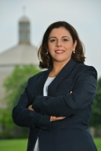 Professional head shot of Maha Saad. She is standing in front of St. Thomas Moore church on a cloudy day. Her arms are crossed in front of her. She is wearing a navy blue blazer, light blue blouse. She is smiling.