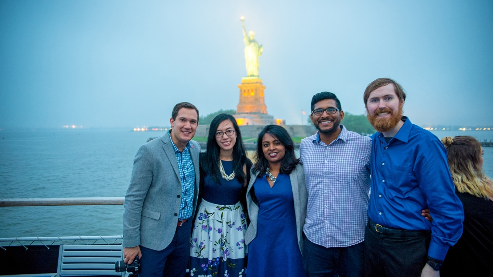 Group of Alumni on boat infront of statue of liberty