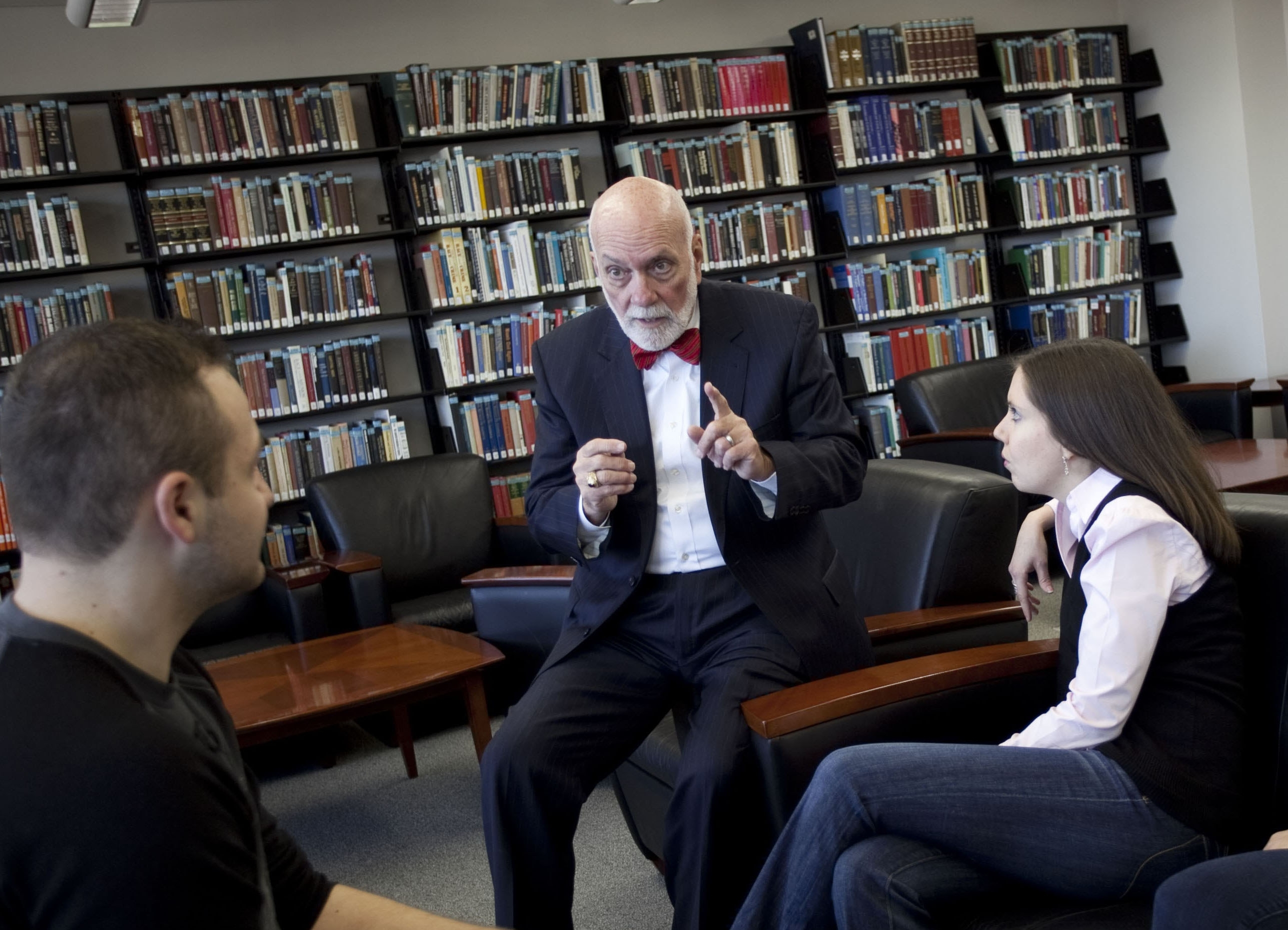 Dean Simons speaking with students in library
