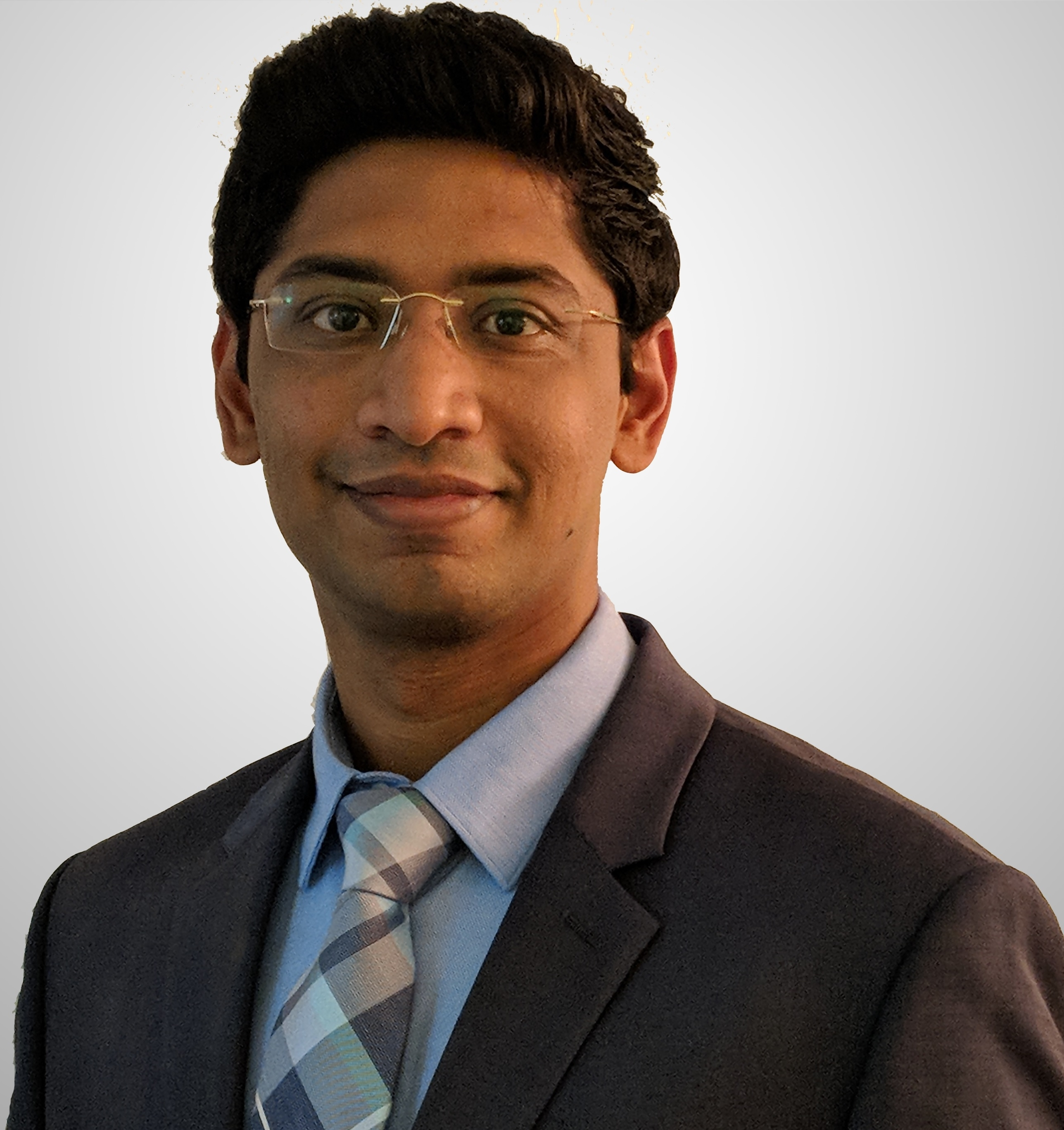 Professional headshot of professor, Dr. Nitesh Kunda in a gray blazer, blue button shirt, plaid tie and white background