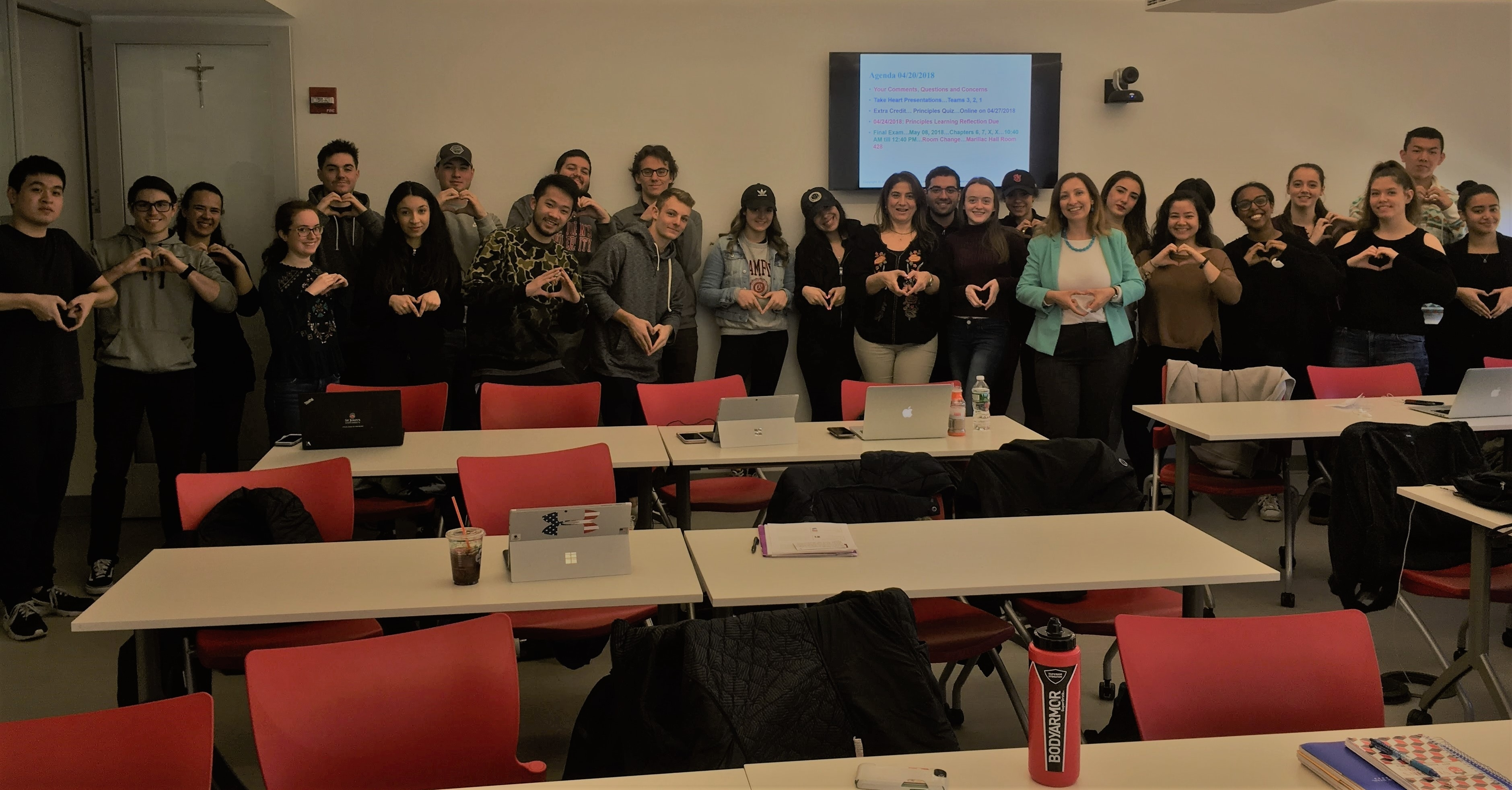 A group photo of students in Prof. Maggiore's class posing with a heart symbol made with their hands, together with Soha Sidhom from Mission Take Heart and Anna Zak from AS-L.