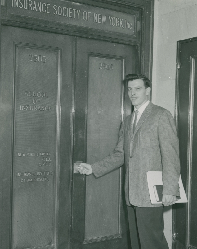 A student walking through the entrance of the Insurance Society of New York on William Street
